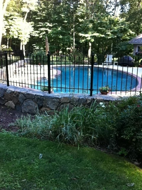 Iron Fence Installed on a Wall Top Surrounding a Pool