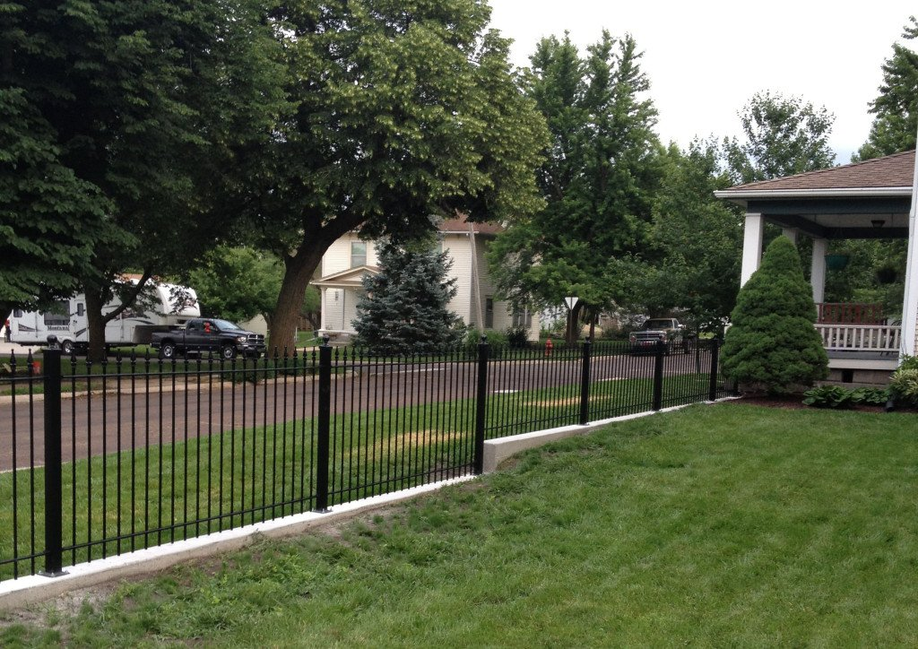 Iron Fence Mounted on a Knee Wall and Stepped for Grade Using Different Heights of Fence