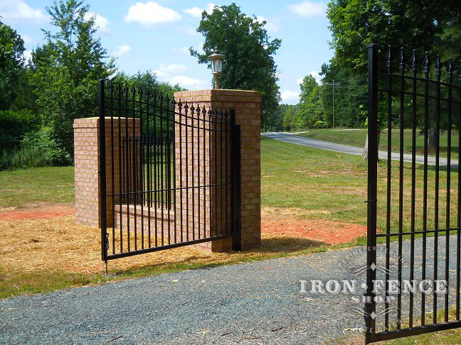 Iron Driveway Gate with Steel Posts Between Brick Pillars