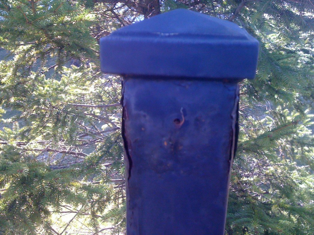 A Non-Galvanized Iron Fence Post Rusting from Below the Finish Causing it to Blister and Come Off