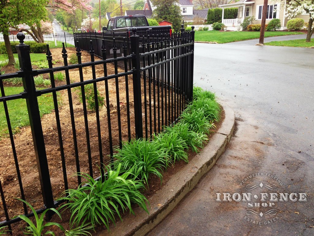 aluminum fence angled around a curb