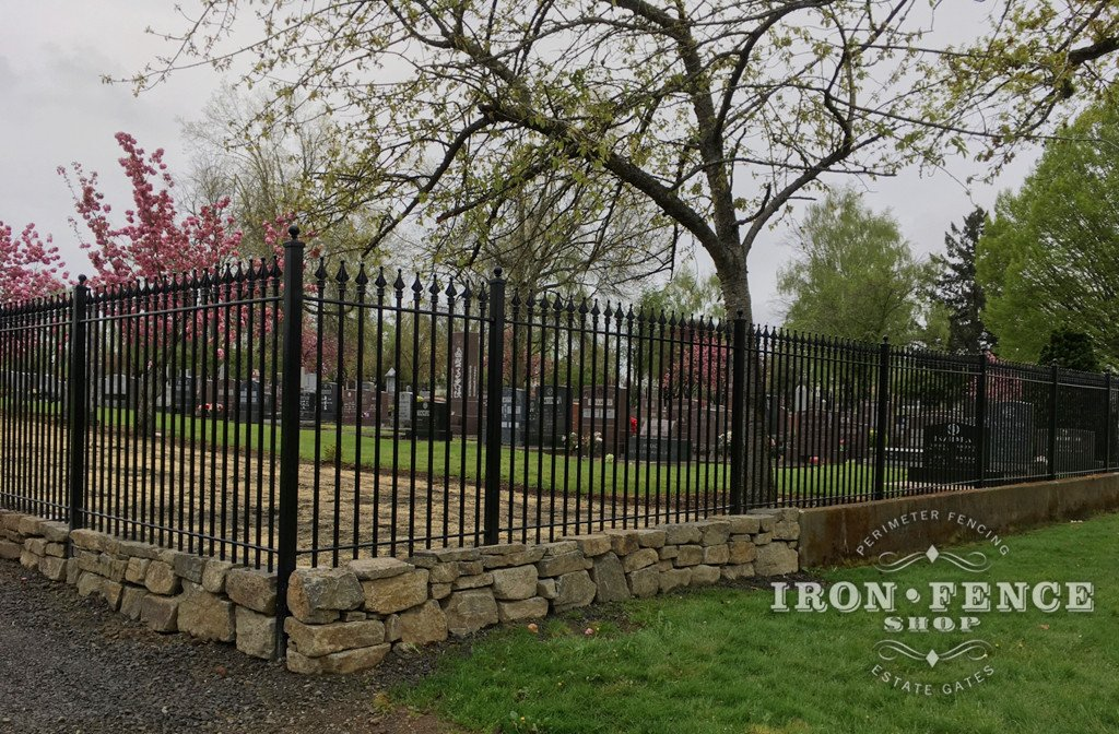 Wrought Iron Fence Surrounding a Cemetery un Conjunction with a Stone Knee Wall