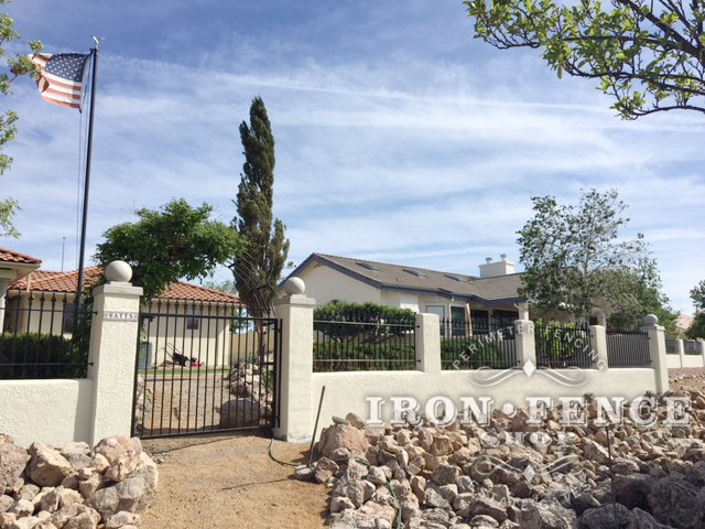 Our Classic style Stronghold Iron fence Mounted on top of a stucco knee wall with matching gate