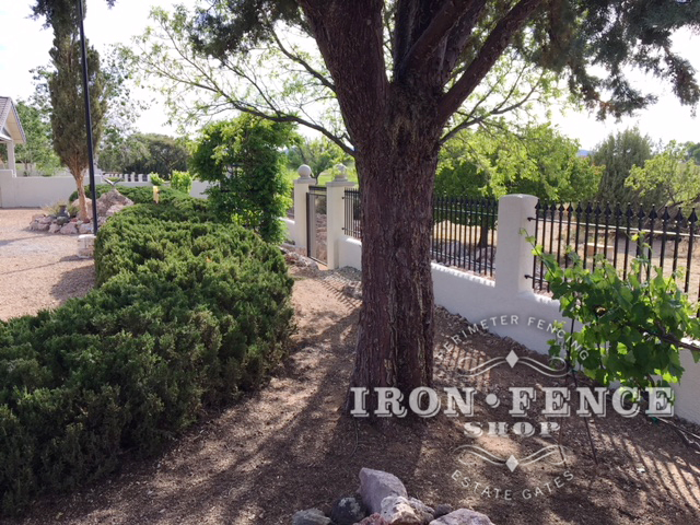 Our Classic style Stronghold Iron fence Mounted on top of a stucco knee wall